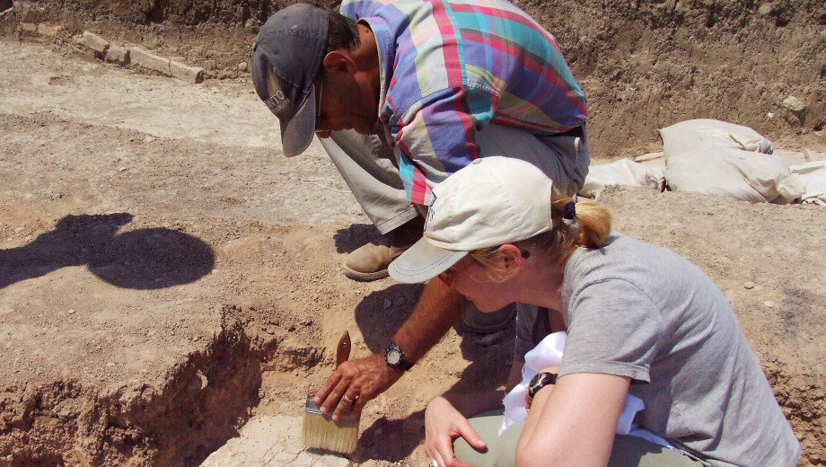 Timothy Harrison and an archaeological team member dust off a find at Tell Tayinat.
