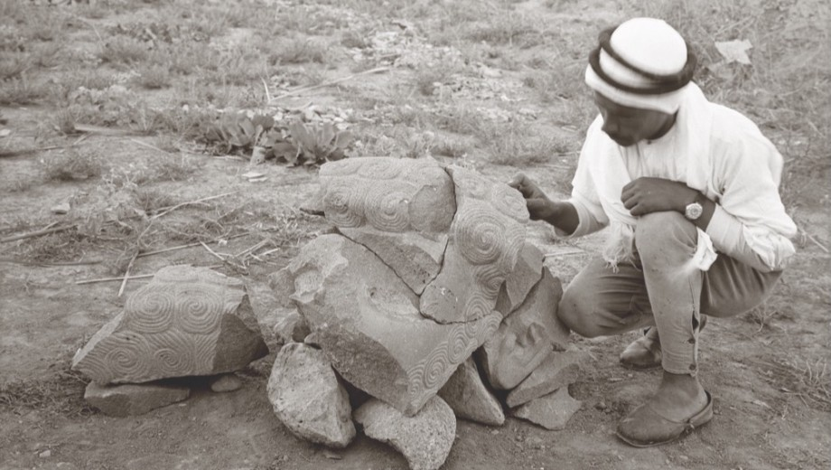 An archaelogist examines an ancient sculpture.