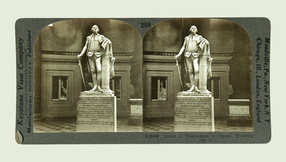 A stereograph card from the early twentieth century shows twin images of a George Washington statue in the United States Capitol.