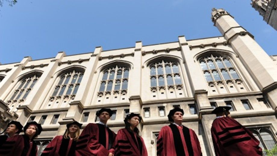Students in graduation robes in front of the Reynolds Club