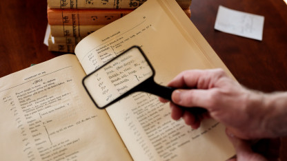 James Nye examines a dictionary with a magnifying glass.